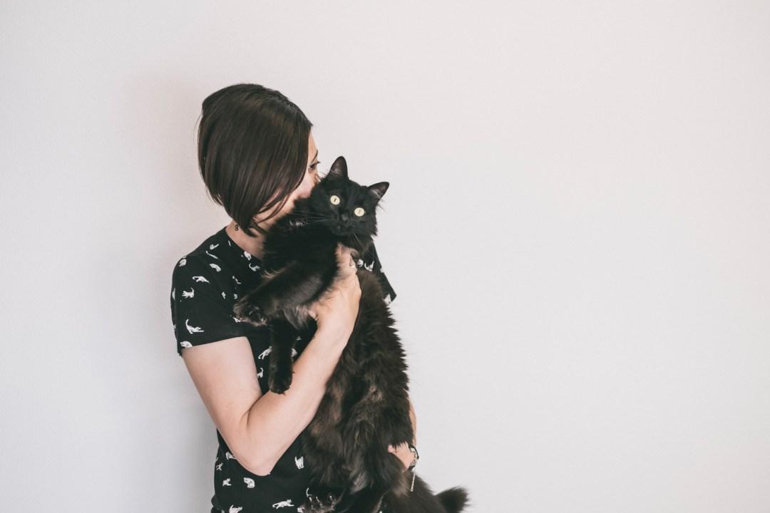 chica besa gato negro pelo largo