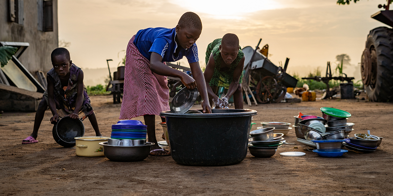 Two girls and their brother wash dishes outside their home in Lome, Togo.