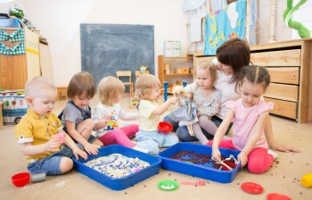 Children with teacher improving hands motor skills in kindergarten