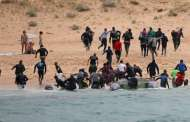 Inmigrantes desembarcan ante la mirada de los turistas