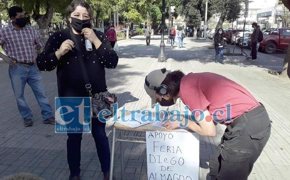 Un transeúnte firmando en apoyo a los chacareros para que vuelva a funcionar la feria.