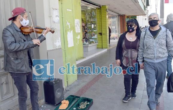 PERSONAJE URBANO.- En la vereda de calle Prat, junto a la farmacia de don Jaime Amar, todos los días se instala este joven violinista a tocar su violín.