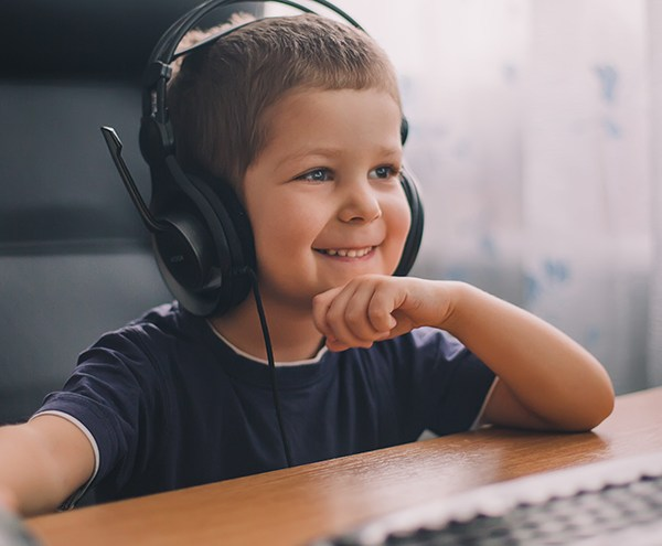Boy wearing headset at computer, smiling while in an eLuma online therapy session