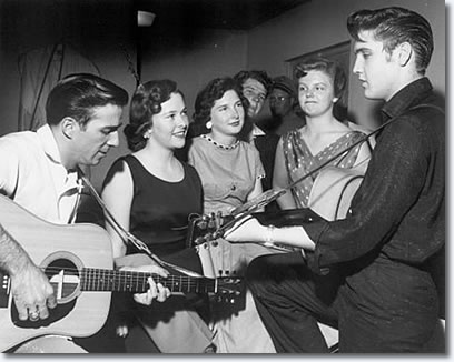 Faron Young and Elvis entertain fans backstage while Jane Giles, Elsie Medlin, Bob Montgomery and Valerie Harms look on