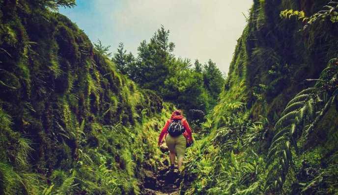 Mujer escalando superandose y llegando a la meta