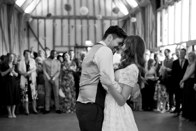 bride and groom smile during first dance as guests watch