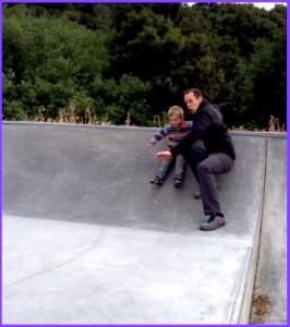 Dad and kid having fun at skate park