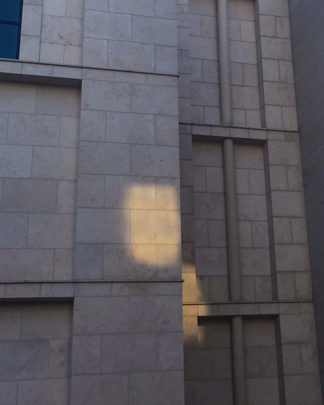 Thumbnail for Readings Image: Cement building with reflected light wrapping around a corner.