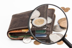 Coins on top of a wallet magnified by a magnifying glass