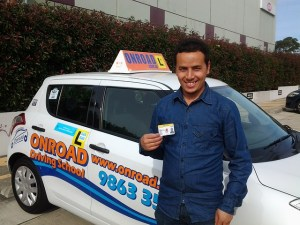 A happy man holding his drivers license card