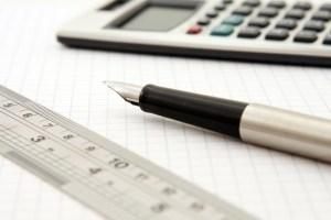 Pen, ruler, calculator on top of a paper