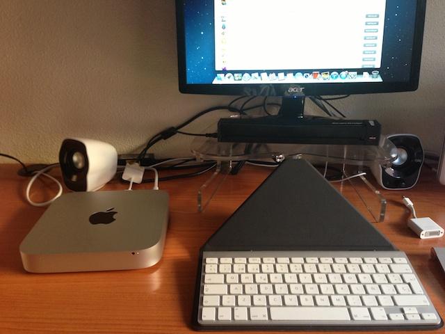 Mac mini conectado a un monitor, con muchos cables por detrás y un teclado inalámbrico en una especie de soporte
