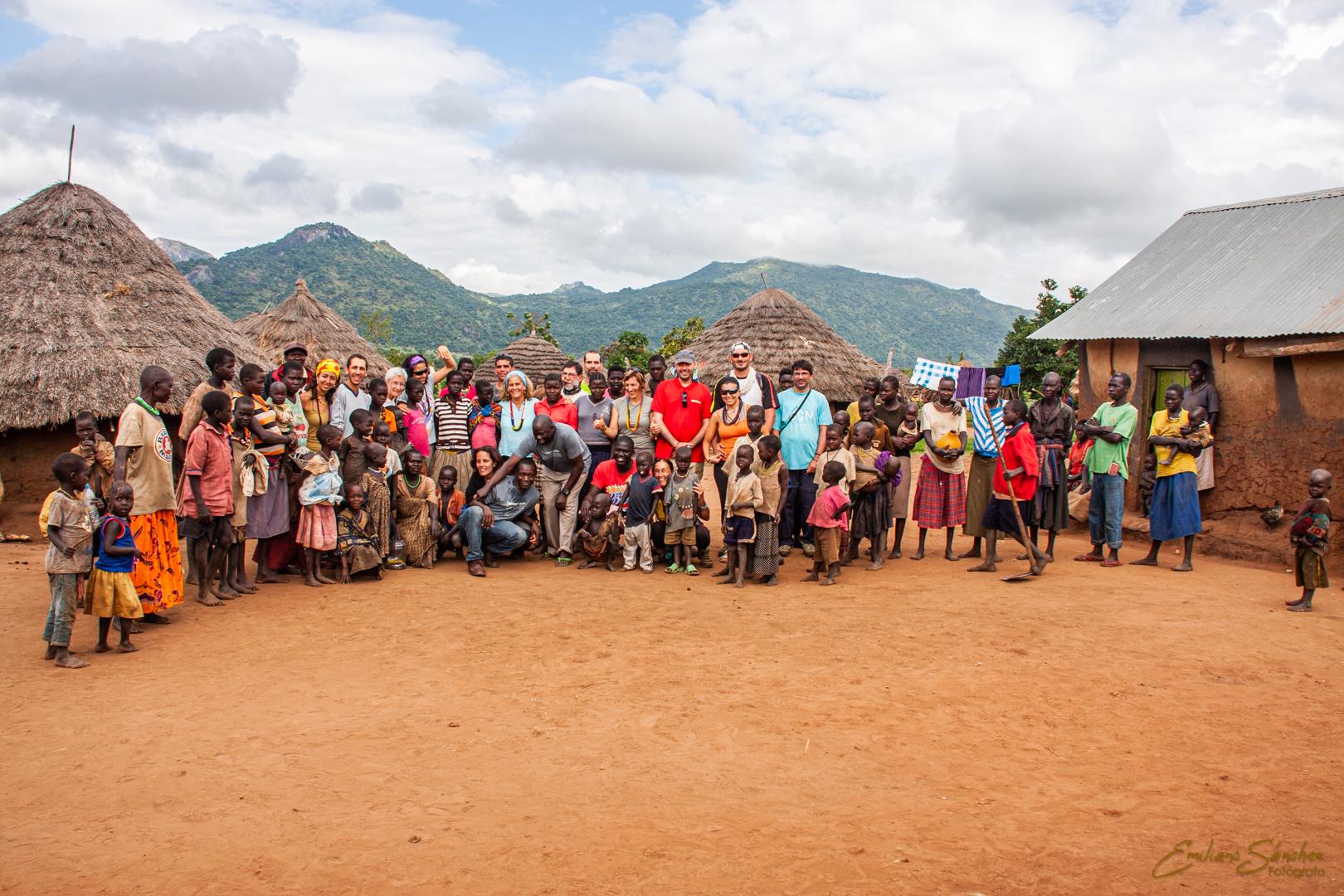 Viajeros del viaje fotográfico a Uganda posando con una tribu.