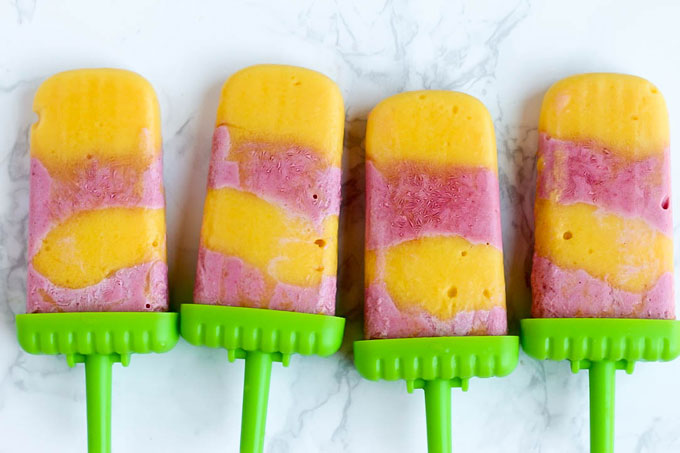Satisfy your sweet tooth with these healthier Vegan Strawberry Orange Mango Popsicles! Only a few ingredients for a delicious treat that will cool you off.