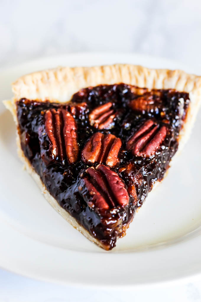 A slice of this Vegan Pecan Pie is all you need this holiday season! The sweet, gooey pecan filling tops a flaky crust that is irresistible. A must-have!