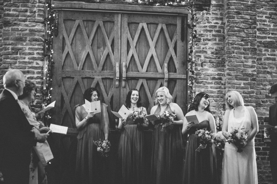 Bride and bridesmaids laughing during the ceremony