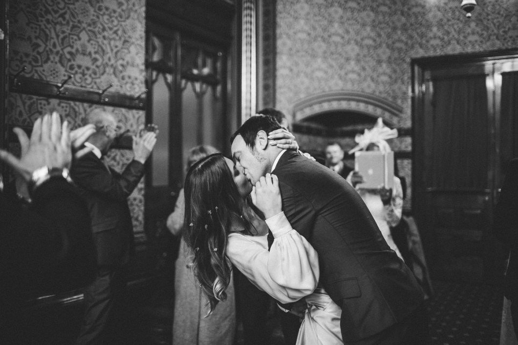Beautiful first kiss with bride wearing flowers in her hair