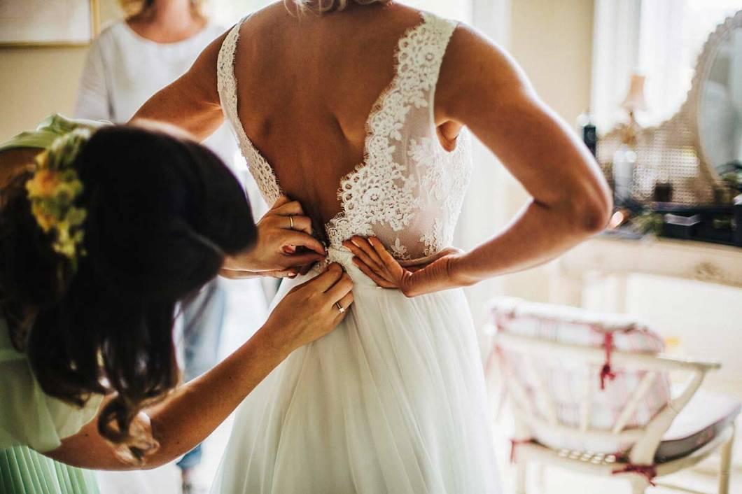 Bride getting into her Mirror Mirror dress