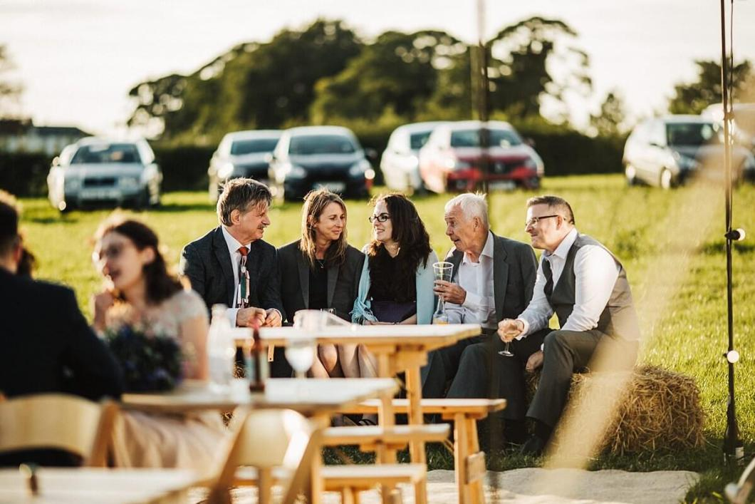 Guests enjoying drinks at the farm wedding