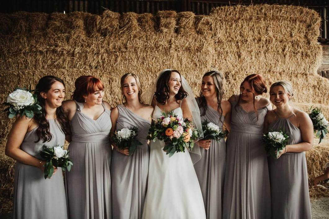 Bridesmaids laughing holding bouquets