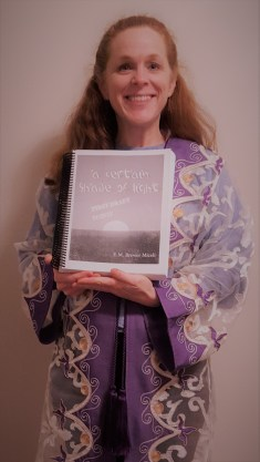 Emily Brewer Miceli in purple and gold Lebanese writing robe with first draft of novel about Queen Athaliah