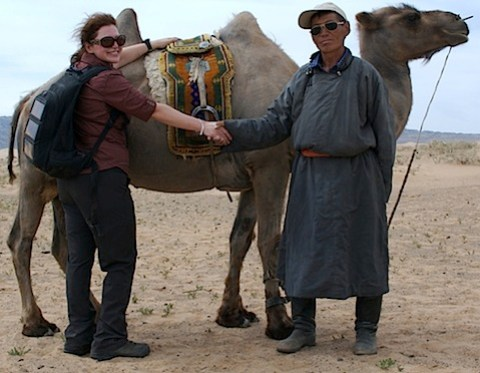 Emily, digital nomad, with Voltaic backpack about to mount camel
