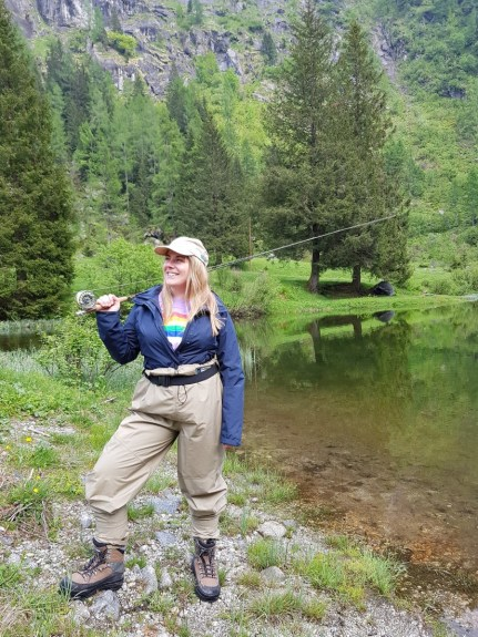 Girl fly fishing in waders by a lake