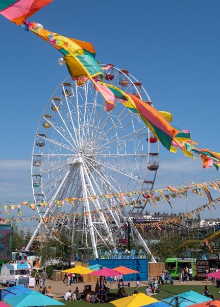 Big Wheel at a Seaside Funfair with Colourful Flags in Foreground