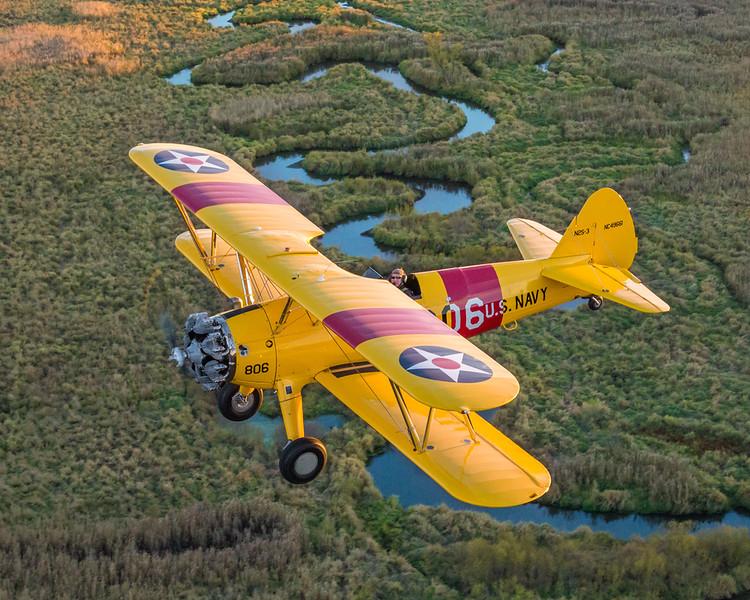 A Boeing Stearman biplane passes over the Rum River near Princeton, Minnesota.