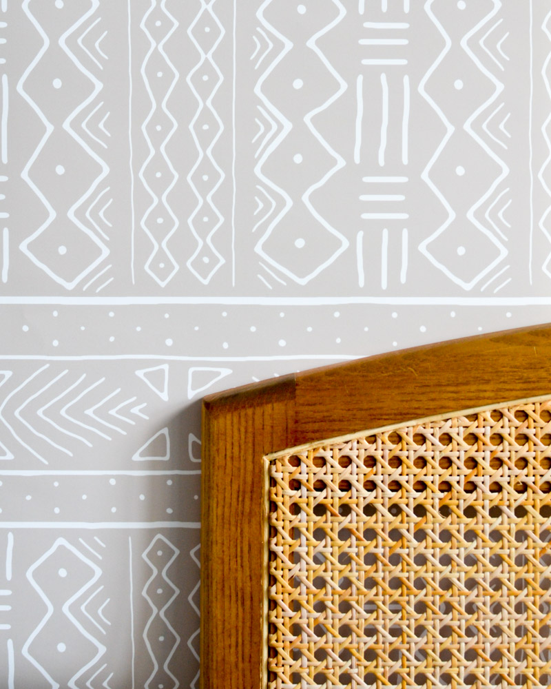Removable mudcloth wallpaper by Domisticate on Spoonflower hung behind wicker headboard