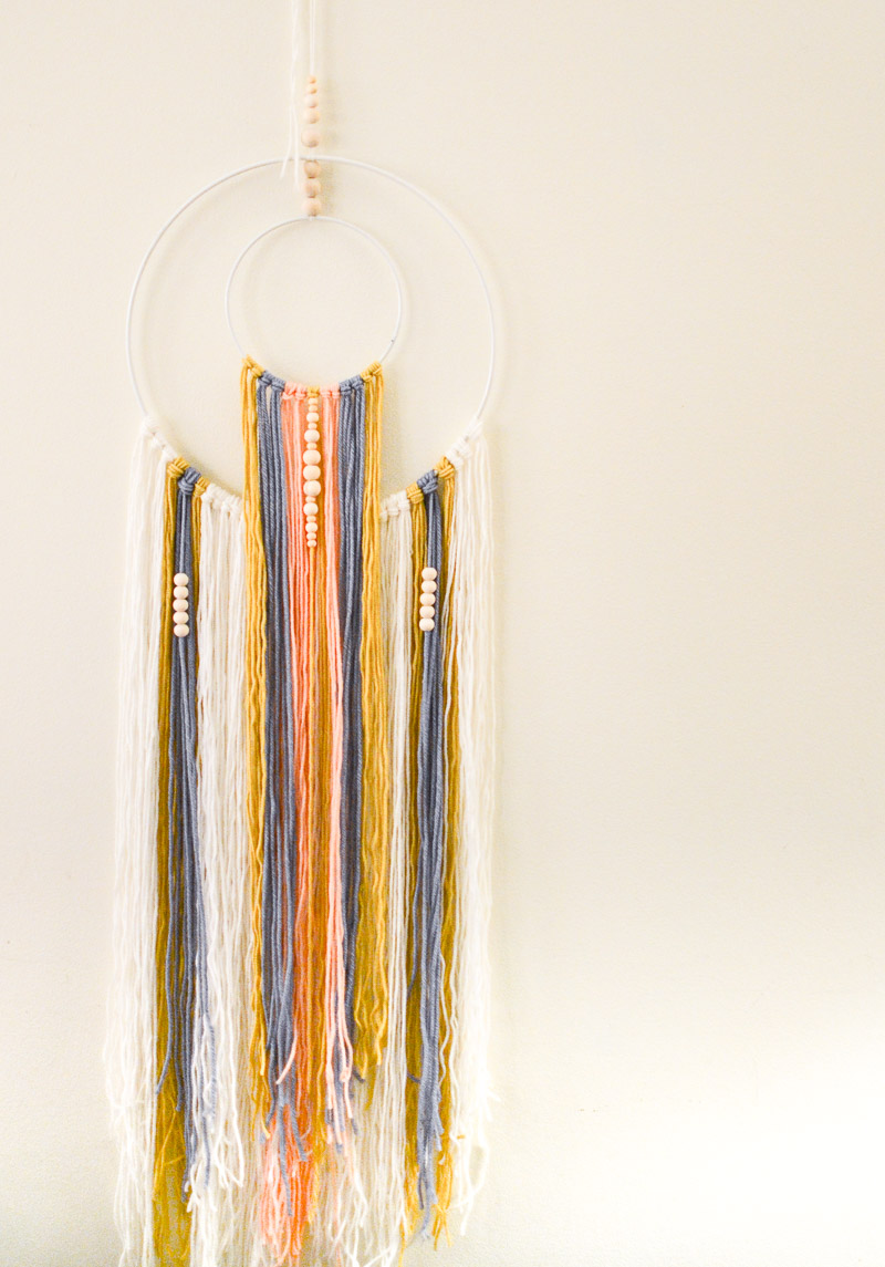 Adding blush yarn details and more wooden beads - DIY wall hanging