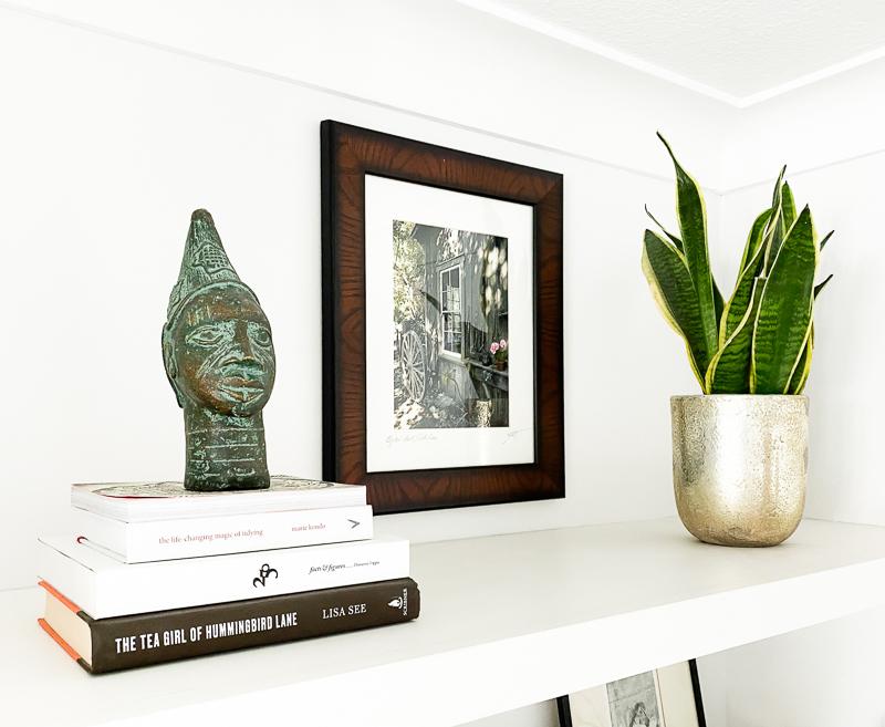African bronze bust & snake plant shelf styling