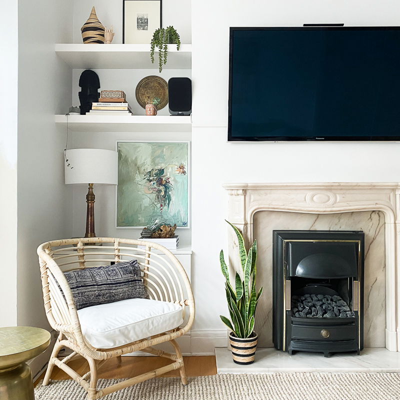 Ikea rattan chair & TV over marble fireplace