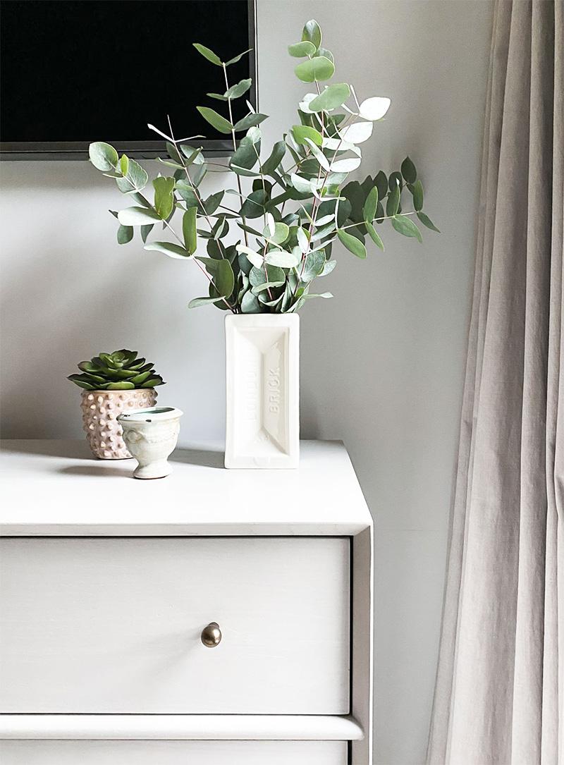 Dresser styling under big TV in bedroom design -Eucalyptus in London brick vase