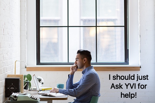 man sitting at desk with computer thinking.
