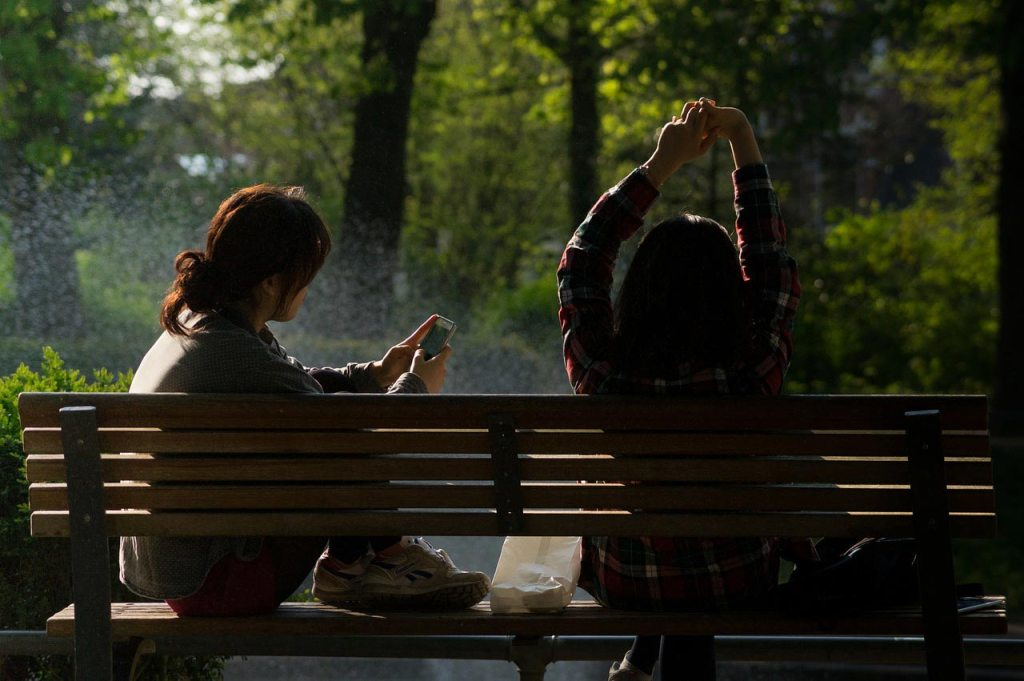 Two women sit on a park bench at the park on a summer day.