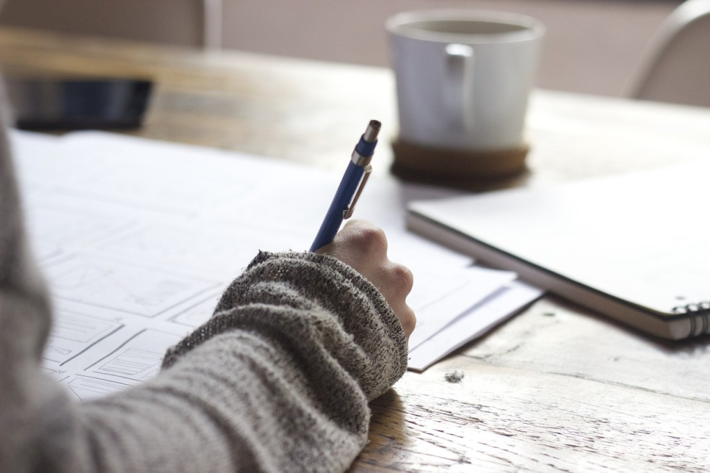 A person sits at a desk, writing into a journal with a pen, and a cup of coffee is in the distance.