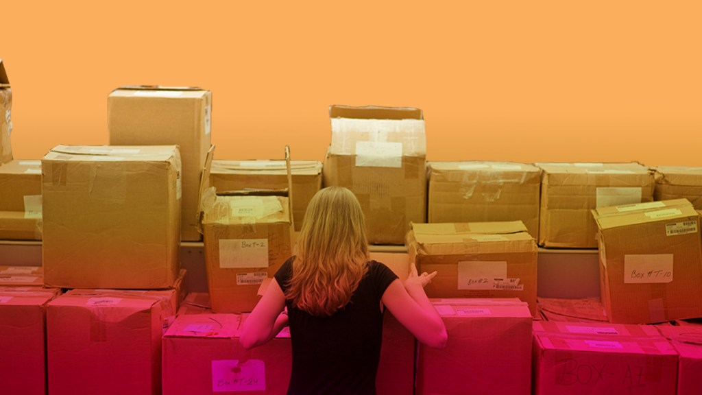 A woman sorts boxes in the storage room all by herself.