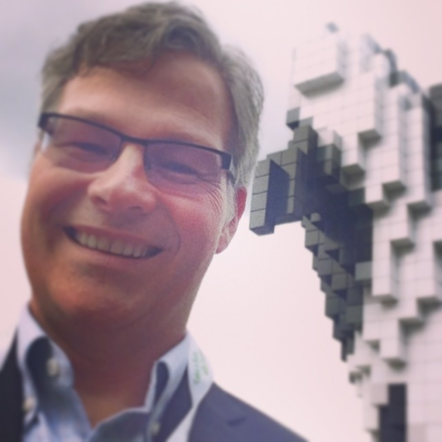 A man is on the left, and we see him from the neck up. He has glasses with black frames, grey hair, and is smiling widely. Behind him there is a sculpture of an orca in breach position, which is out of focus, and seems to be made up of black and white squares like lego.