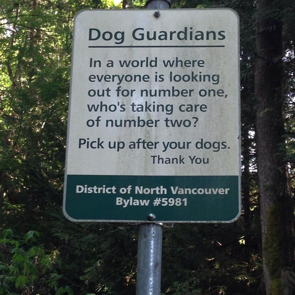 "A white sign with a green stripe on the bottom against a background of green foliage. It says ""Dog Guardians: In a world where everyone is looking out for number one, who is taking care of number two? Please pick up after your dogs, thank you."""