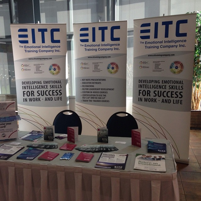Three rectangular backdrops that say EITC and have a graphic of the circular EQ competencies chart. There is a table with a light pink skirt and two black chairs behind it in front of the backdrop.