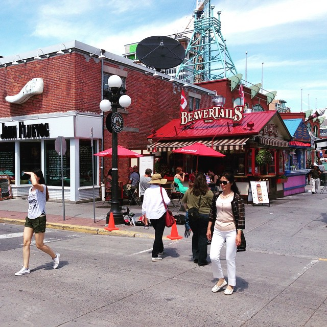 A street corner with a red BeaverTails stand across the road and a red brick building beside it. The sky is bright and blue.