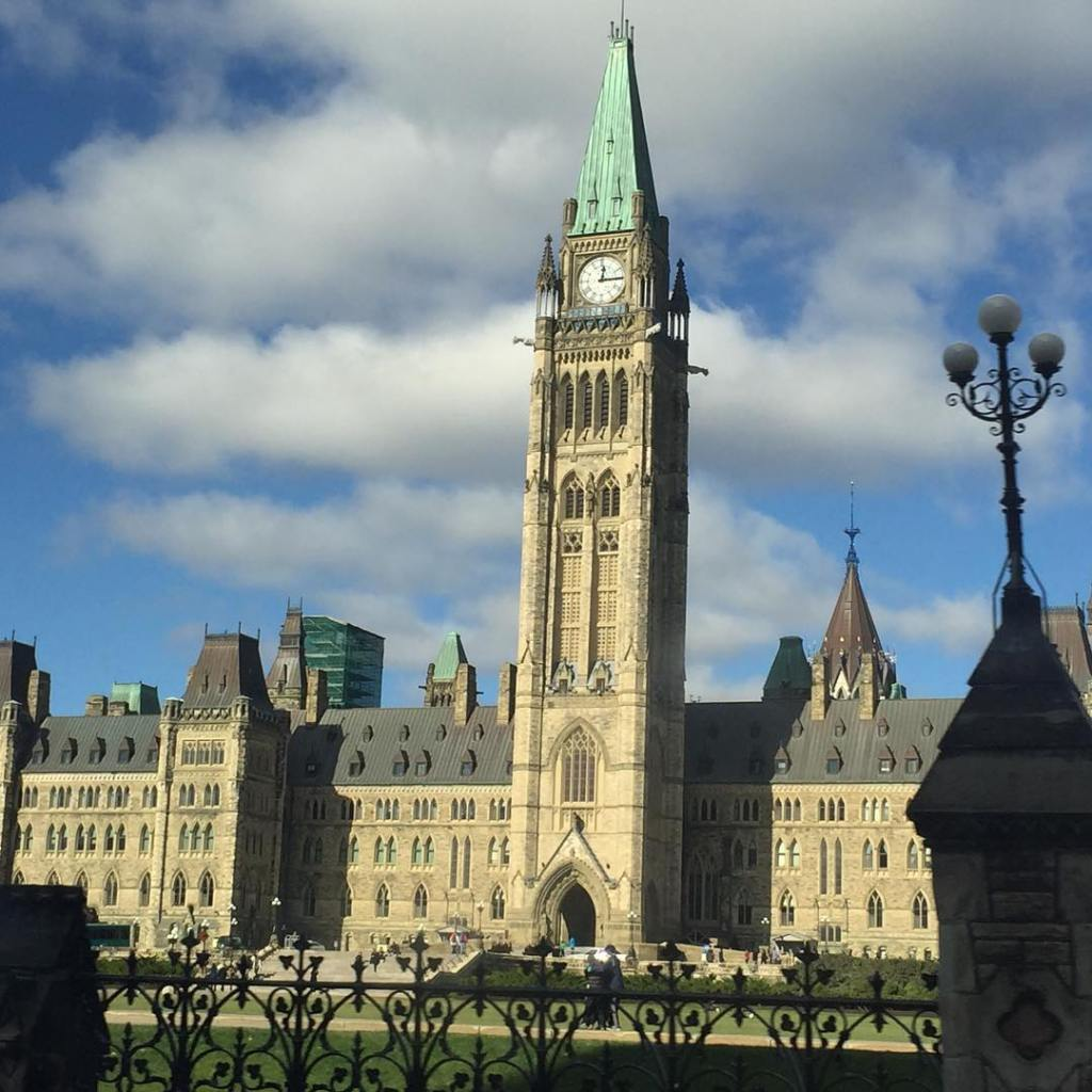 The colonial style stone parliament buildings in Ottawa, which have teal metal roofing atop the tall clocktower that goes up the center. The sky is bright and blue with white clouds.