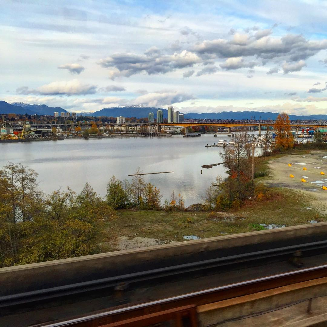 Railroad tracks in the foreground with the ocean in the middle and then downtown Vancouver on the other side with mountains in the background. The sky is blue and cloudy.