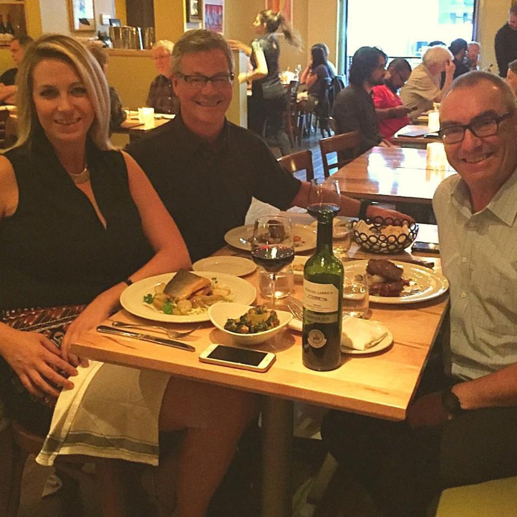 Three people sitting around a square, light brown wooden table covered with food. On the right side is a man with grey hair and black glasses who is smiling. On the other side are a woman with shoulder length blonde hair, and a man with grey hair and black glasses who are also both smiling.