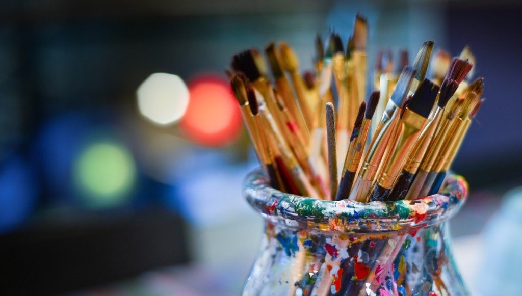 Many brushes in a glass jar with blurred lights in the background at night.