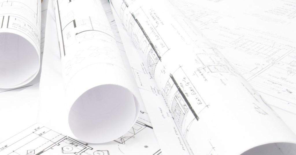 Rolled up blueprints rest on a desk.