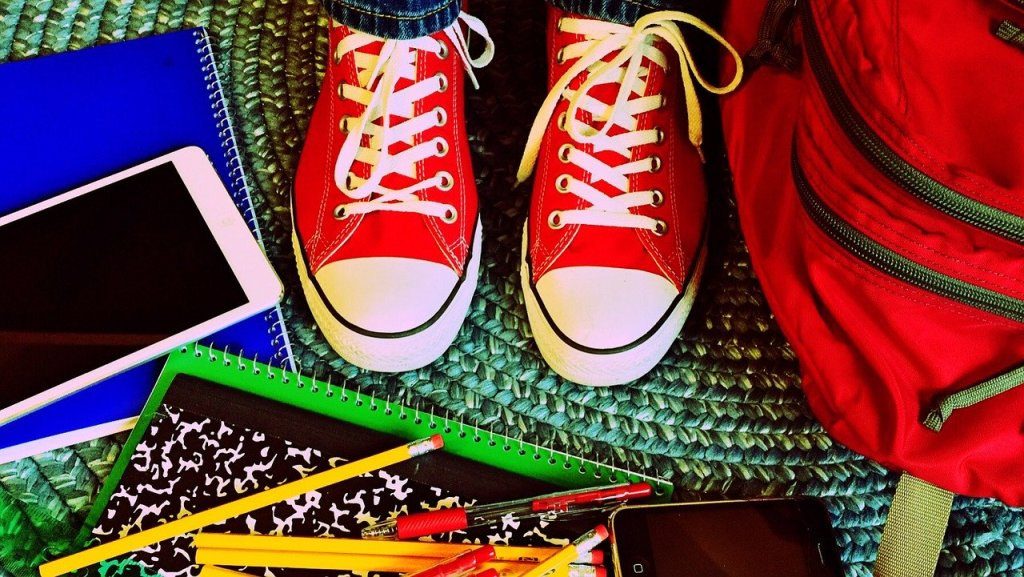 Someone in red sneakers stands in the middle of a rug surrounded by scattered school supplies.