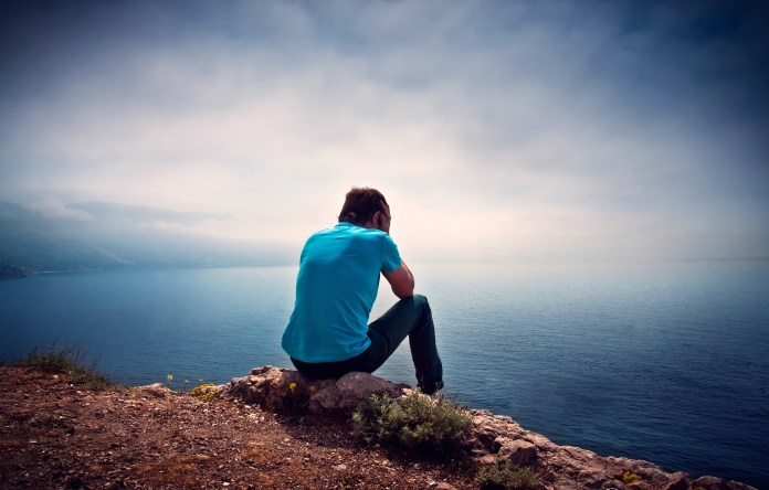 Sad lonely boy on a hill overlooking the sea