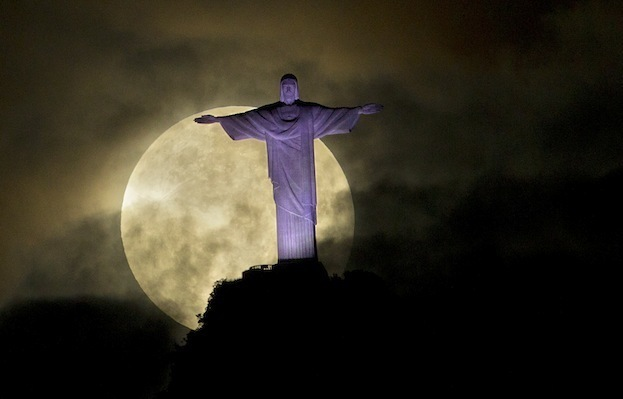 "A ""supermoon"" is seen behind the Christ the Redeemer statue in Rio de Janeiro, Sunday, May 6, 2012. A supermoon is the coincidence of a full moon (or a new moon) with the closest approach the moon makes to the Earth. (AP Photo/Victor R. Caivano)"